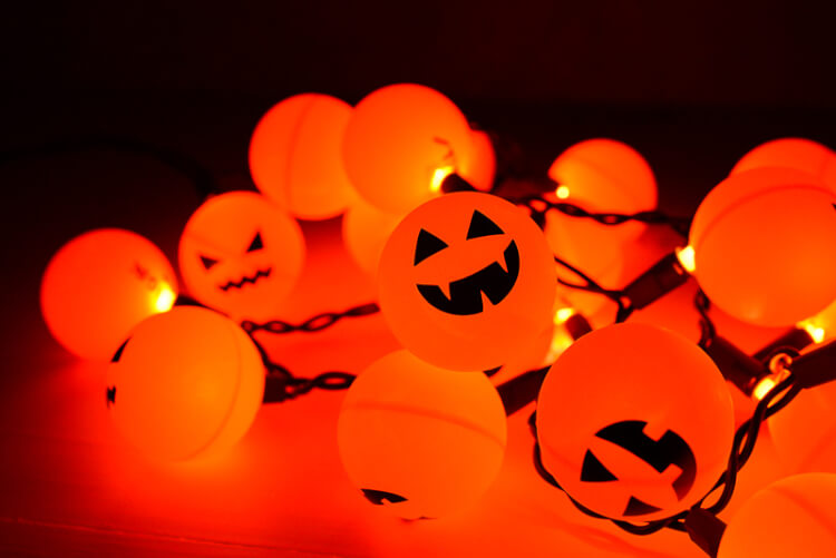 Orange ping pong balls plus fairy lights equal a fun Halloween Jack O' Lantern decoration! An easy project anyone can do.
