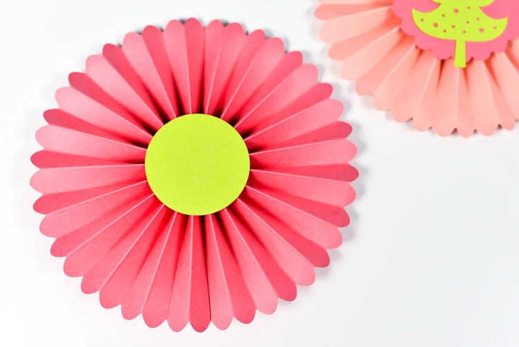 Use hot glue to glue the small circle to the BACK of your rosette.