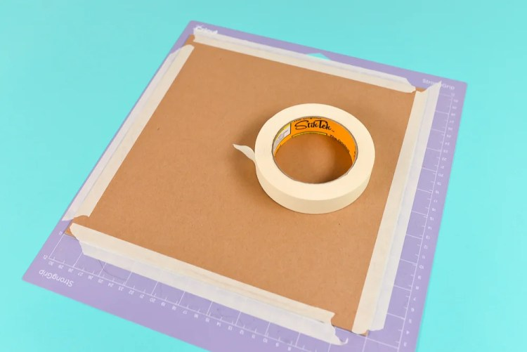 Use masking tape to secure your chipboard to the mat