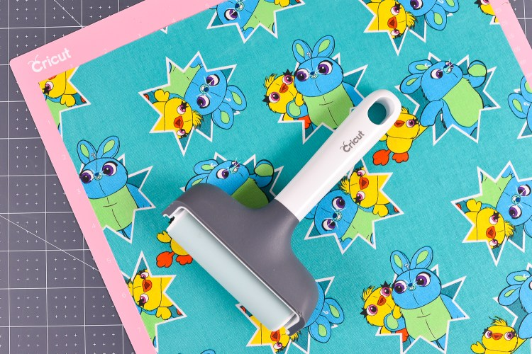 Use the brayer to get your fabric to stick to your mat.