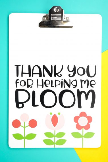 """Say thank you to a favorite educator with this sweet and easy teacher gift idea! Use your Cricut Explore or Maker to make this clipboard, which says """"thank you for helping me bloom,"""" along with cute Scandinavian-style flowers."""