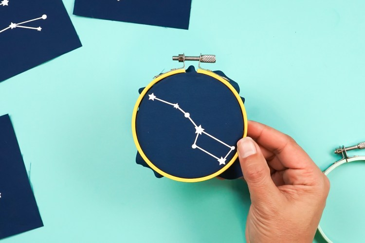 Then take the outer piece of the embroidery hoop and slide it over the inner hoop, sandwiching the fabric all the way around. Tighten the screw.
