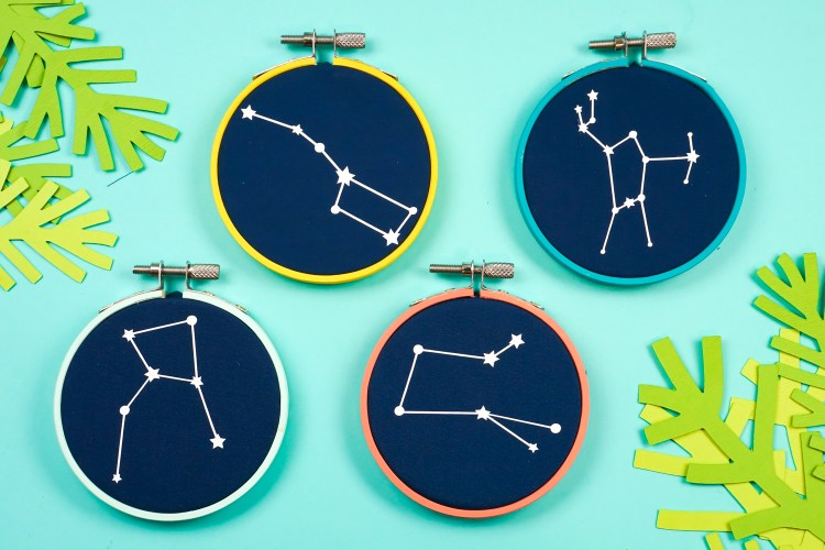 Love the look of embroidery hoop ornaments...but lack sewing skills? Iron on vinyl to the rescue! Use your Cricut or other cutting machine to make these quirky constellation embroidery hoop Christmas ornaments!