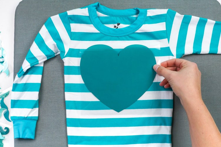 Place the heart decal on the pajama top.