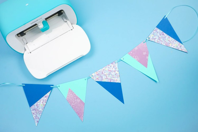 Cricut Joy machine and paper pennants made with the Cricut Joy and Cricut Adhesive Backed Paper