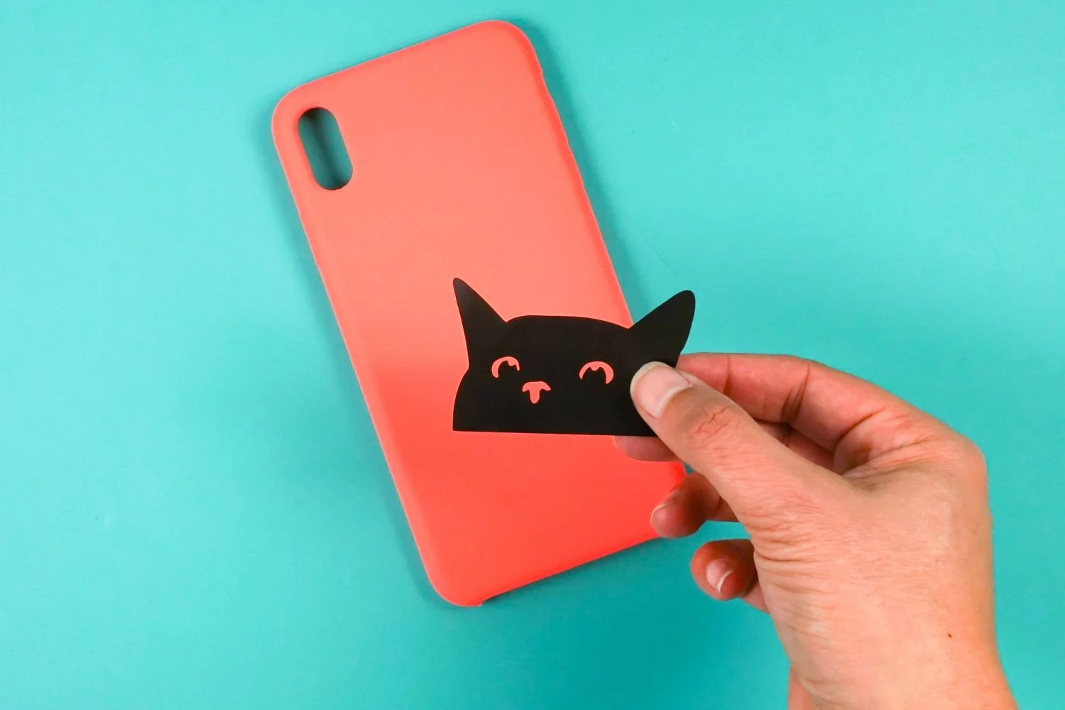 Placing the cat image on the phone by hand.