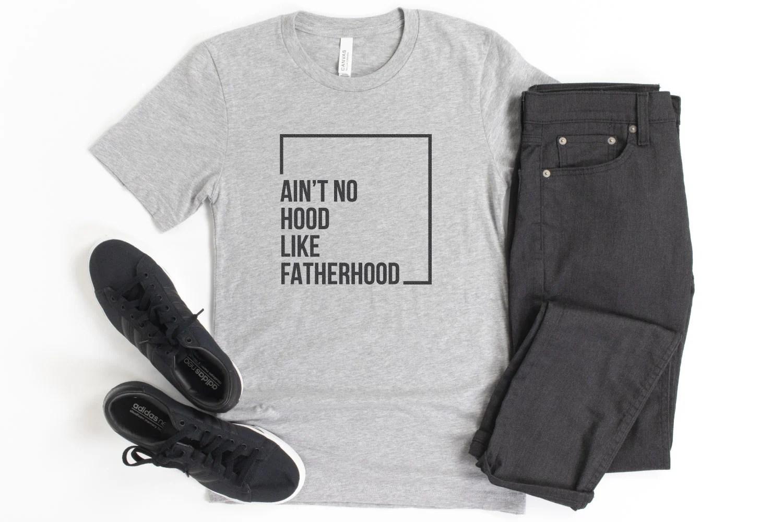 """""""Ain't No Hood Like Fatherhood"""" SVG on a gray shirt with black pants."""