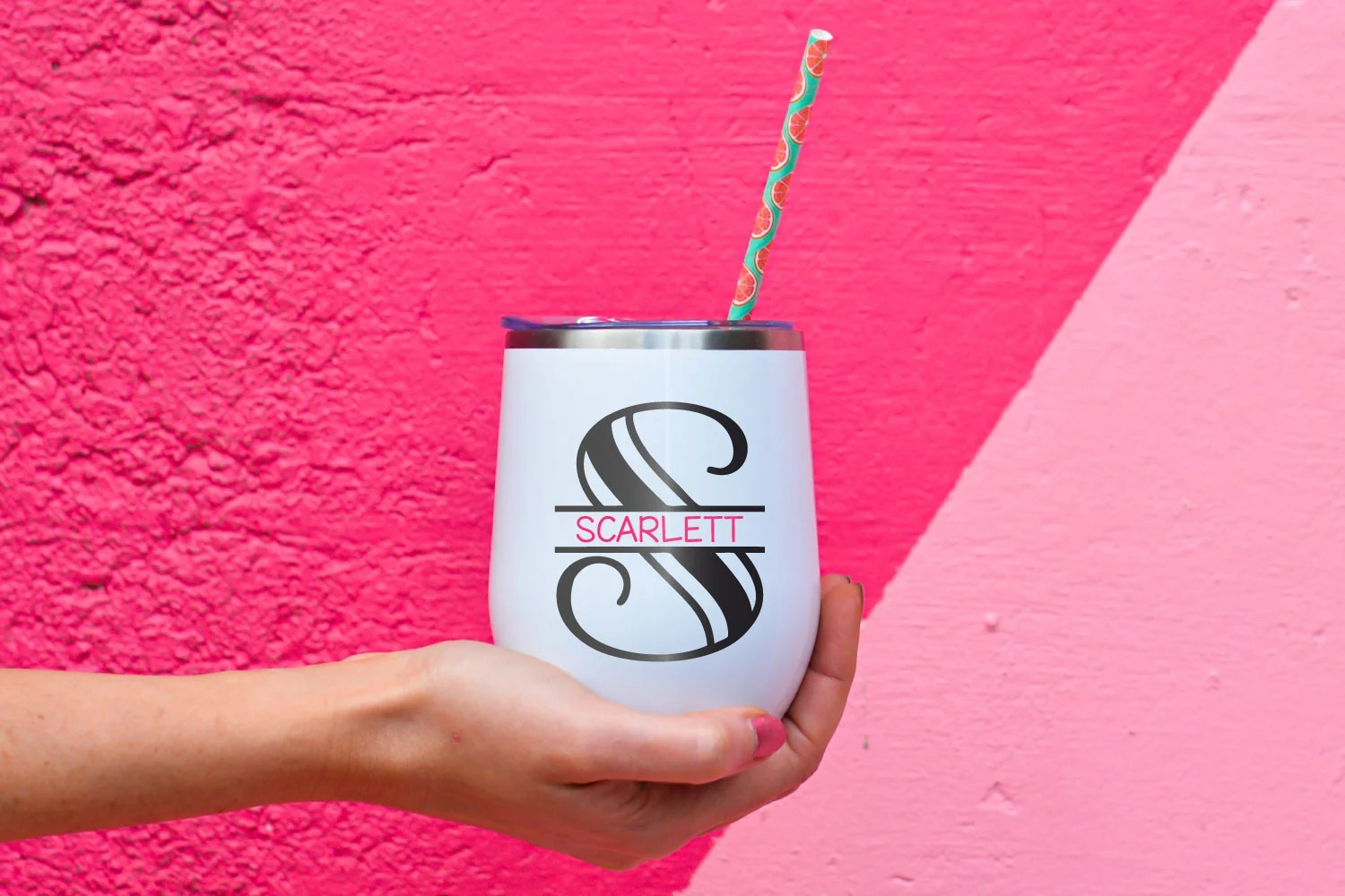 Finished monogram on a wine tumbler on a pink background.