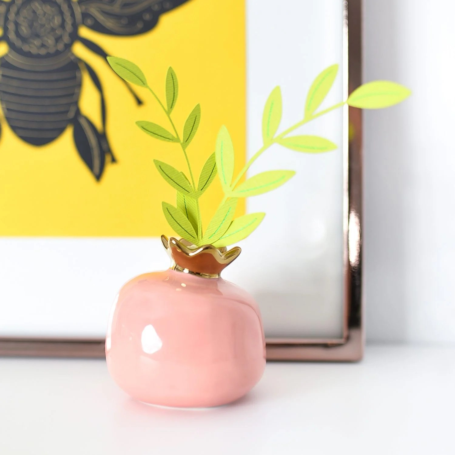 Close up of foiled plant in pink bud vase.