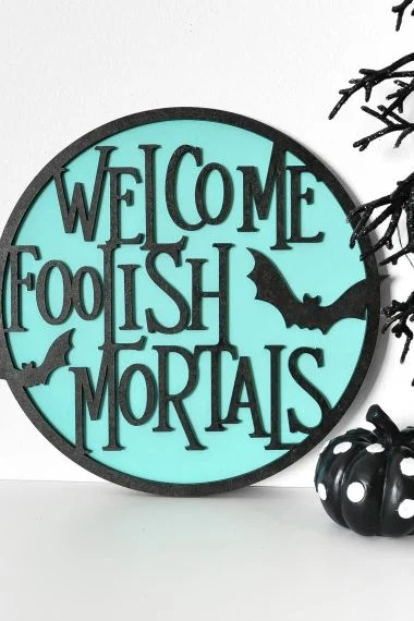 """""""Welcome Foolish Mortals"""" sign made on the Glowforge on a shelf with Halloween decor"""