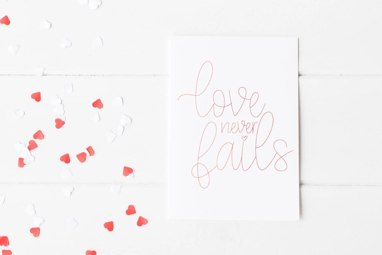 Love Never Fails foiled on a card.