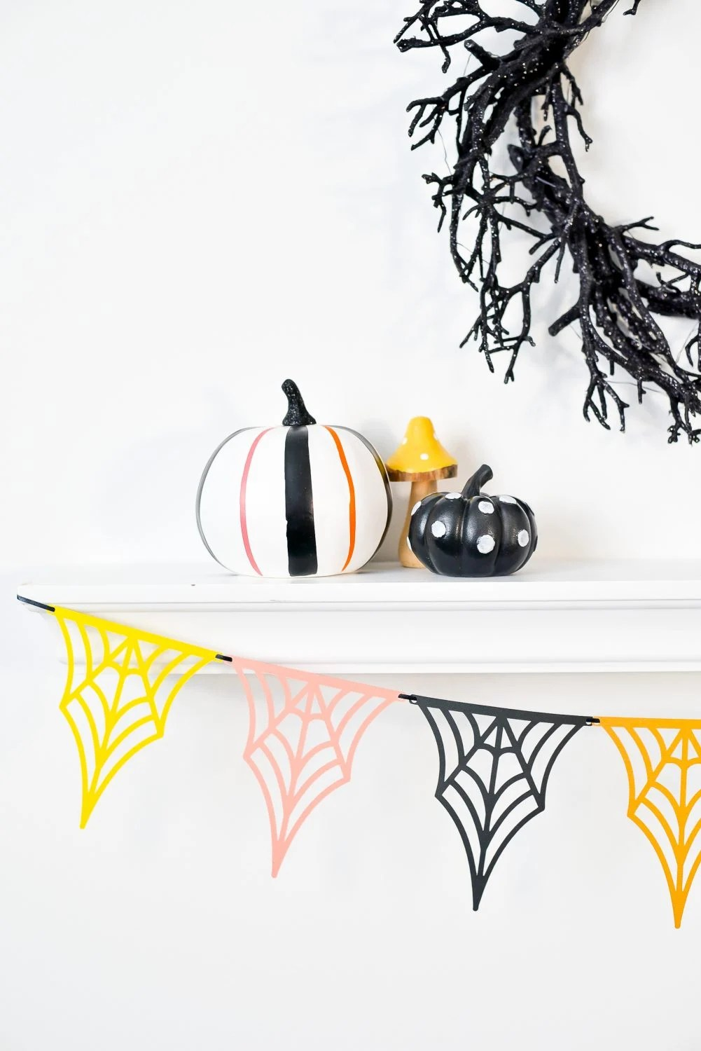 Close up of web banner hanging from shelf with Halloween pumpkins