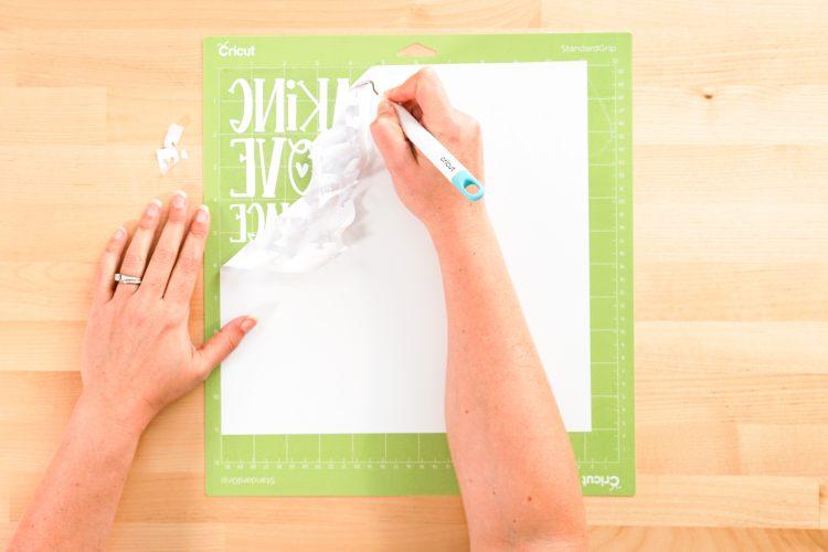 Hands weeding white iron on vinyl decals