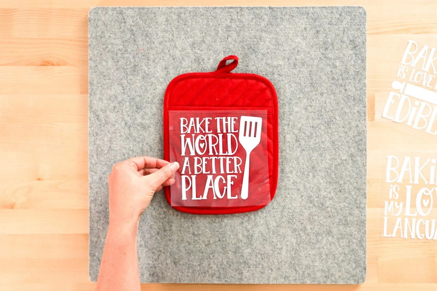 Hand placing decal on pot holder
