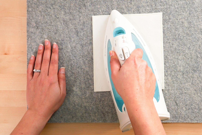 Hands ironing the HeatnBond to the felt.