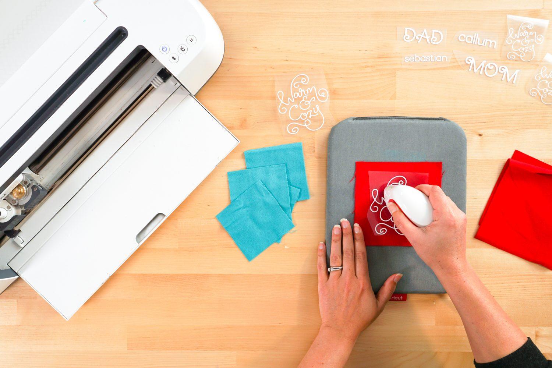 Hand using Easy Press MIni to adhere iron on vinyl