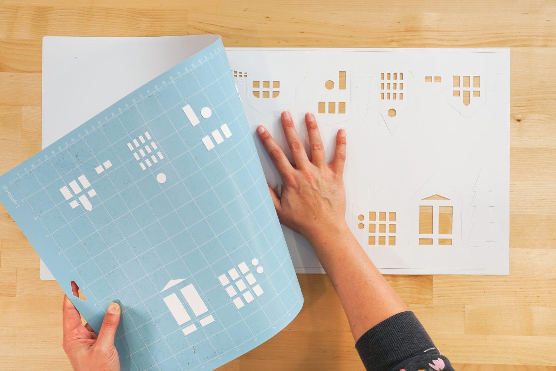 Hands removing paper village from Cricut mat