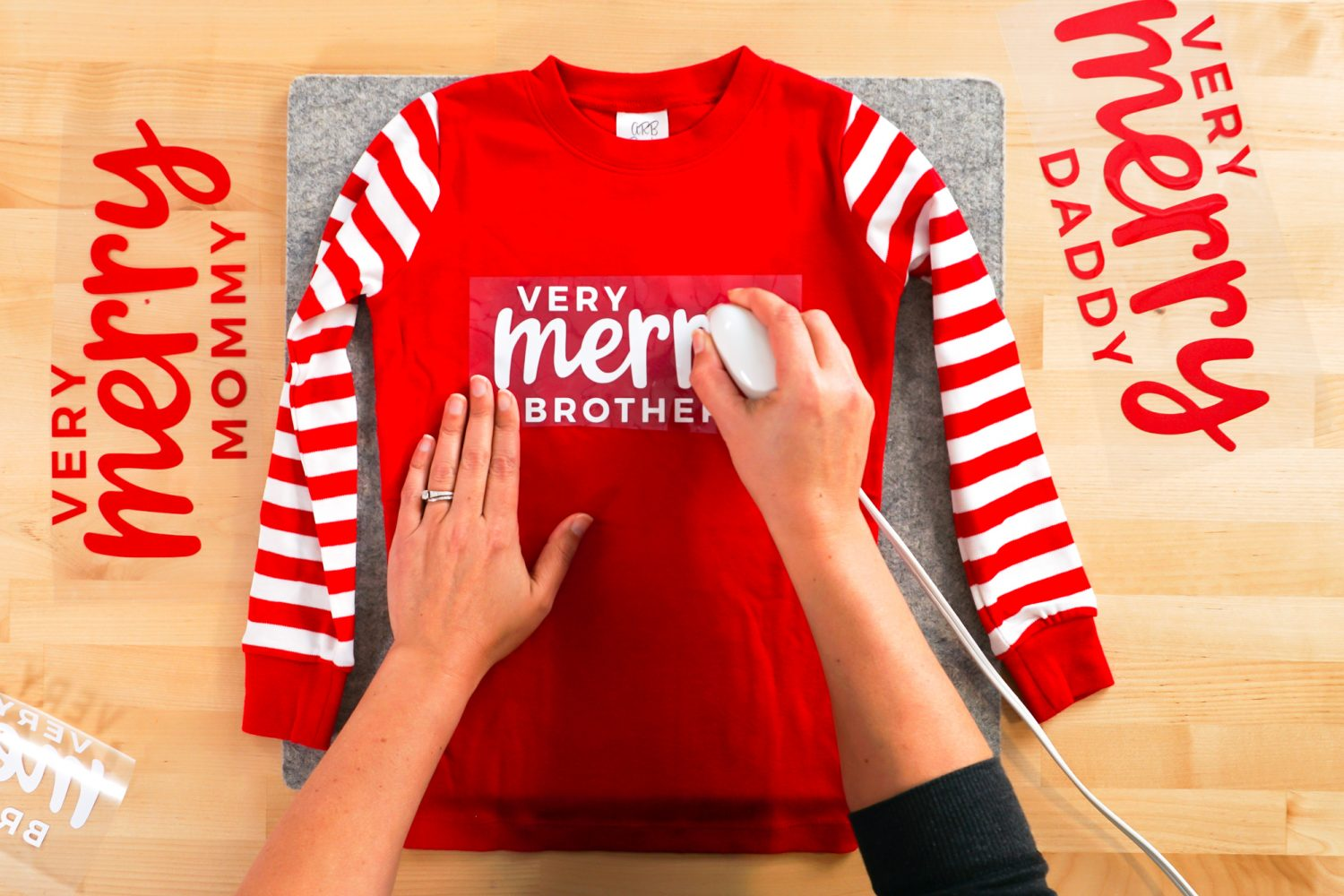 Hands ironing Very Merry Brother decal to shirt