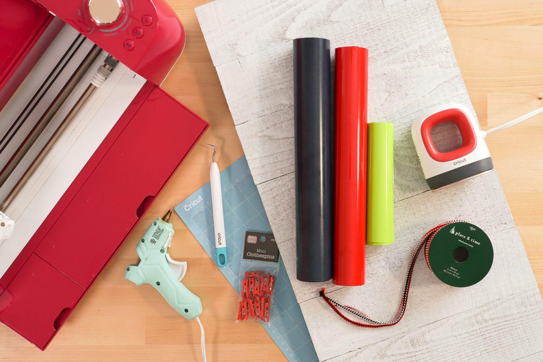 All the supplies needed for this post: Cricut, Cricut mat, iron on vinyl, EasyPress Mini, glue gun, weeding tool, ribbon, tiny clothespins, wood sign