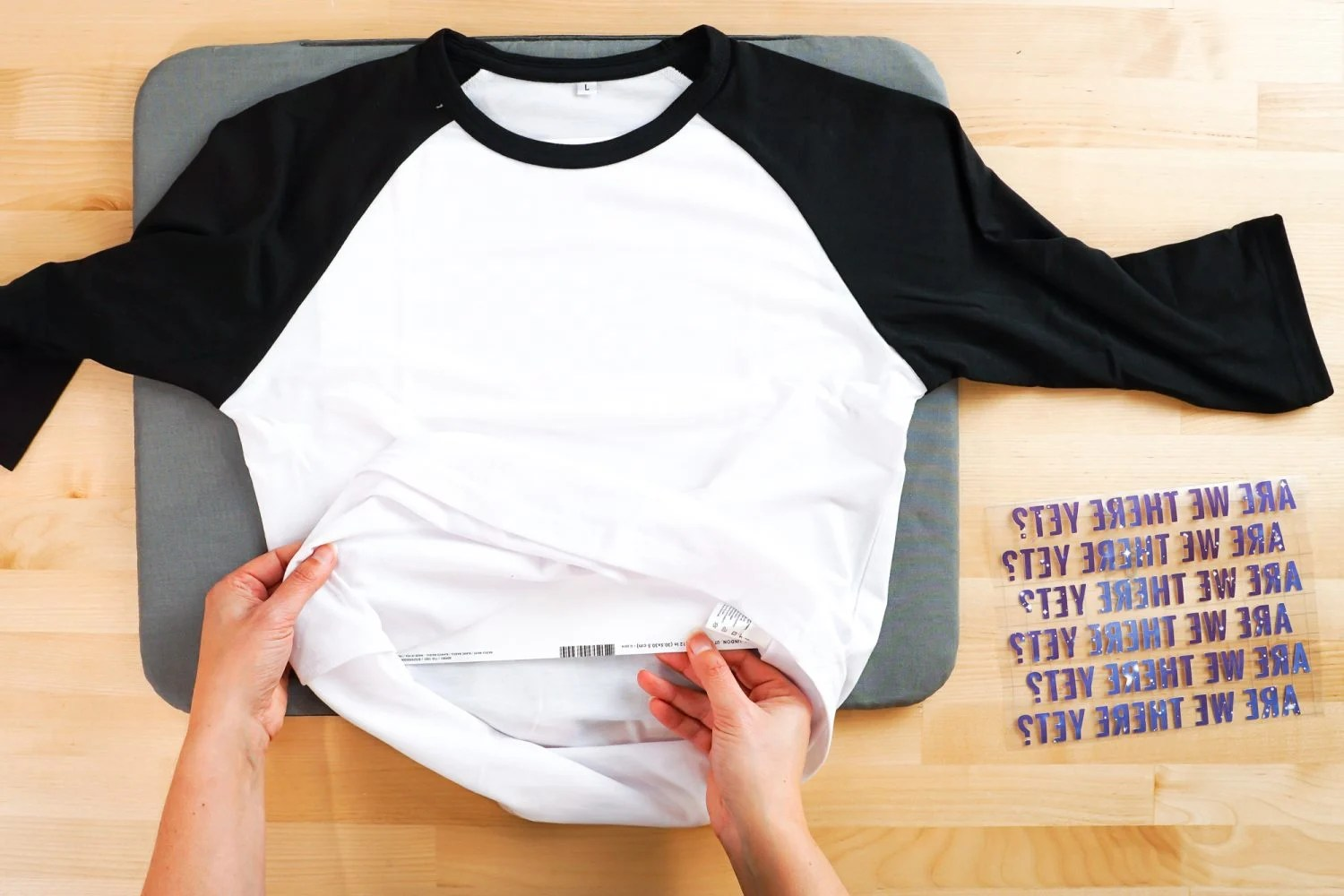 Hands putting a piece of white cardstock in the Cricut Infusible Ink raglan.