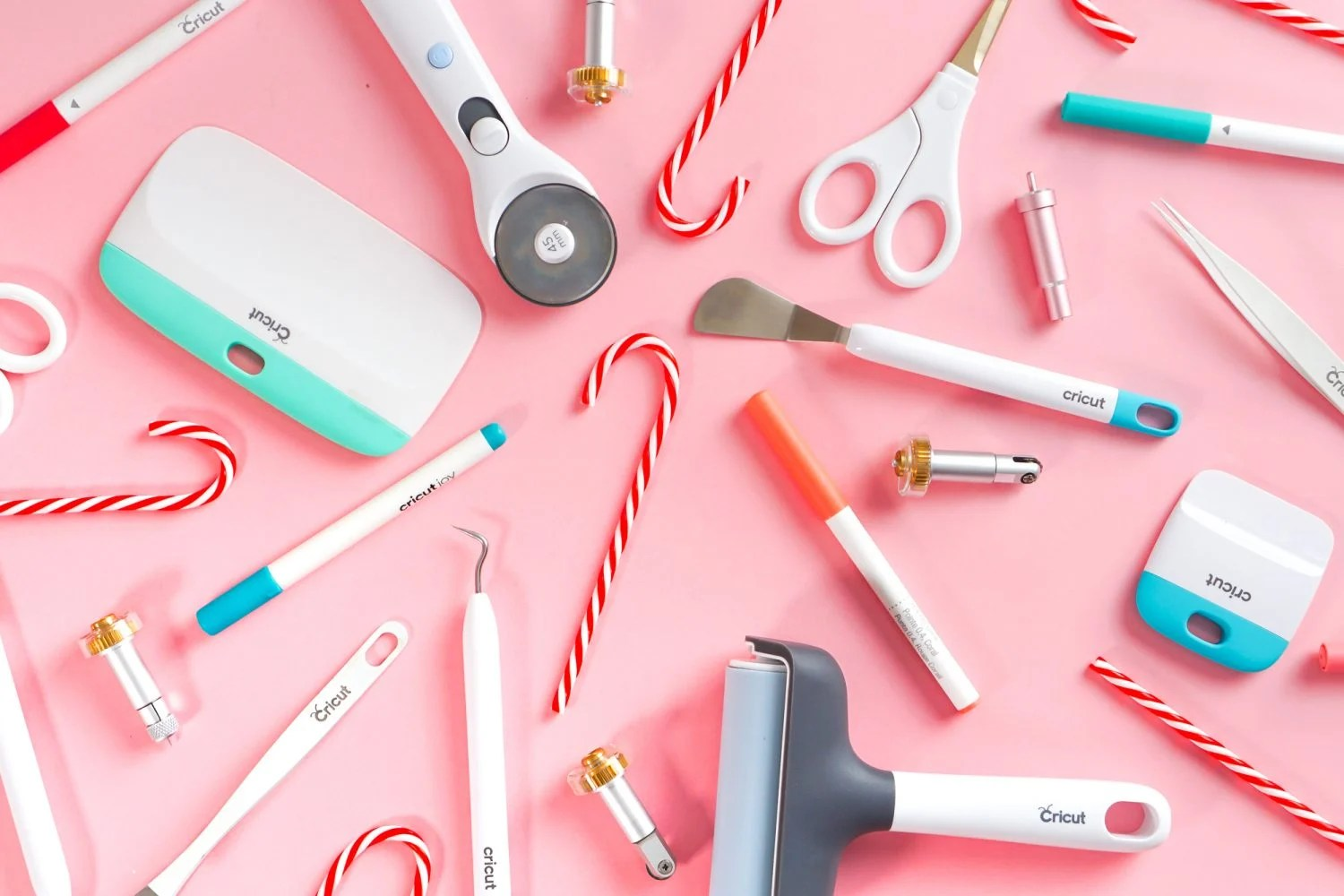 Cricut accessories and candy canes on a pink background