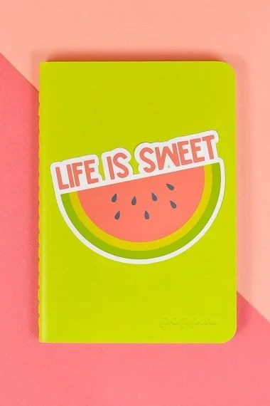 Life is Sweet watermelon sticker on green notebook on pink background