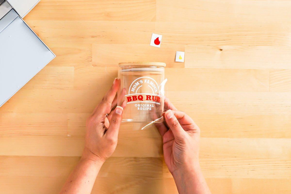 Hands peeling back transfer tape.