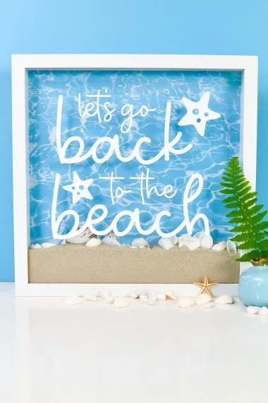 """Finished shadow box with """"Back to the Beach"""" decal, sand, shells, and staged with a plant"""