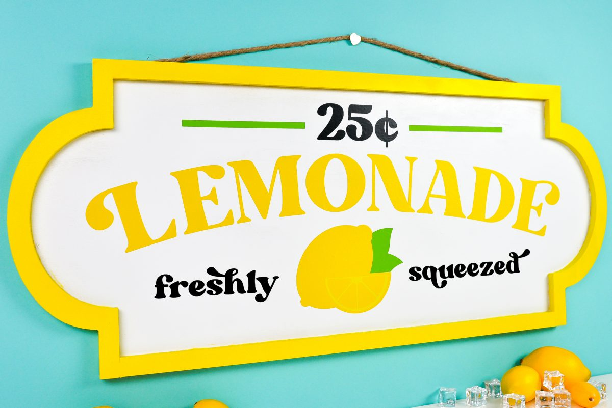 Finished lemonade stand sign on teal background styled with faux lemons and ice