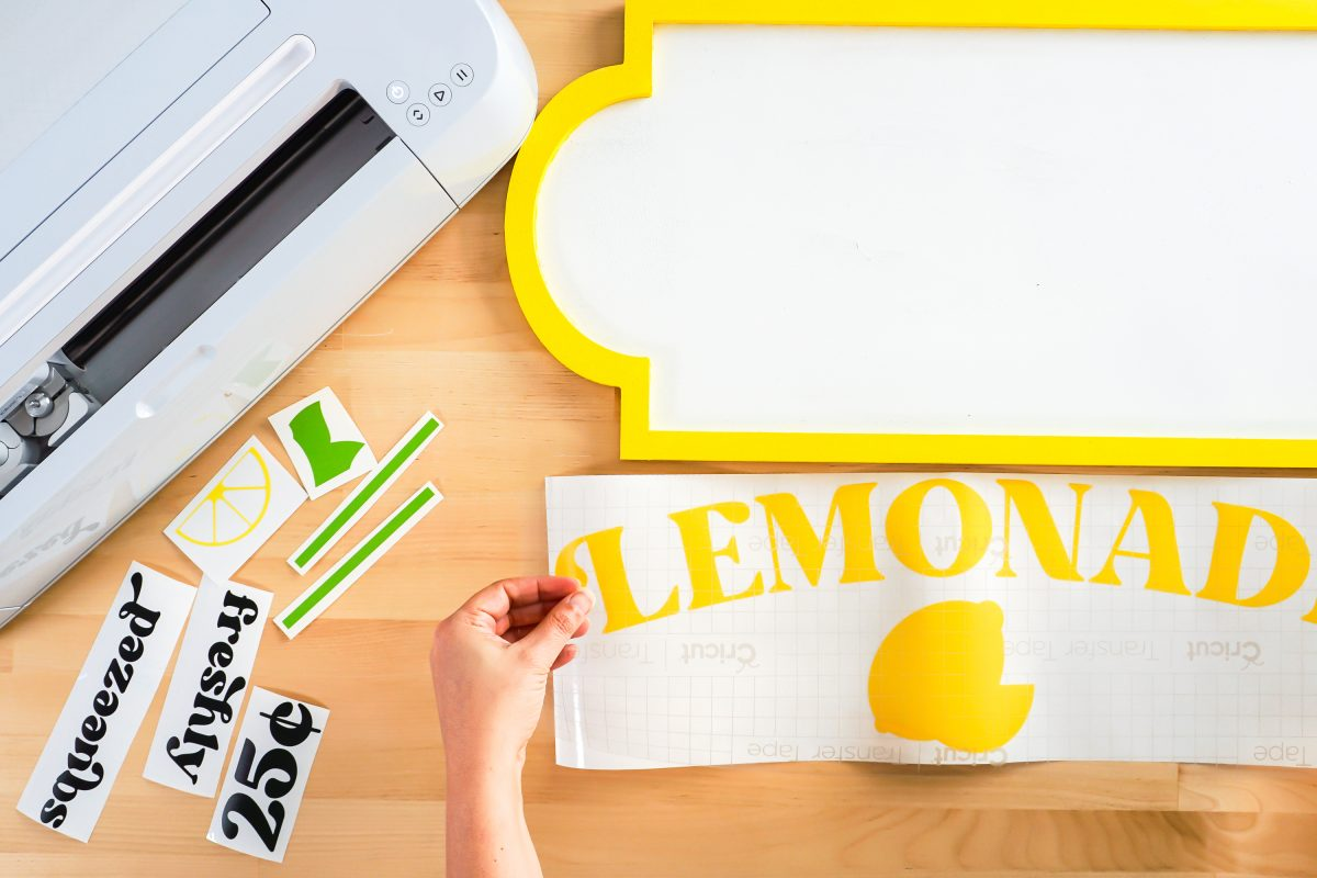 Hands applying transfer tape to large lemonade decal.