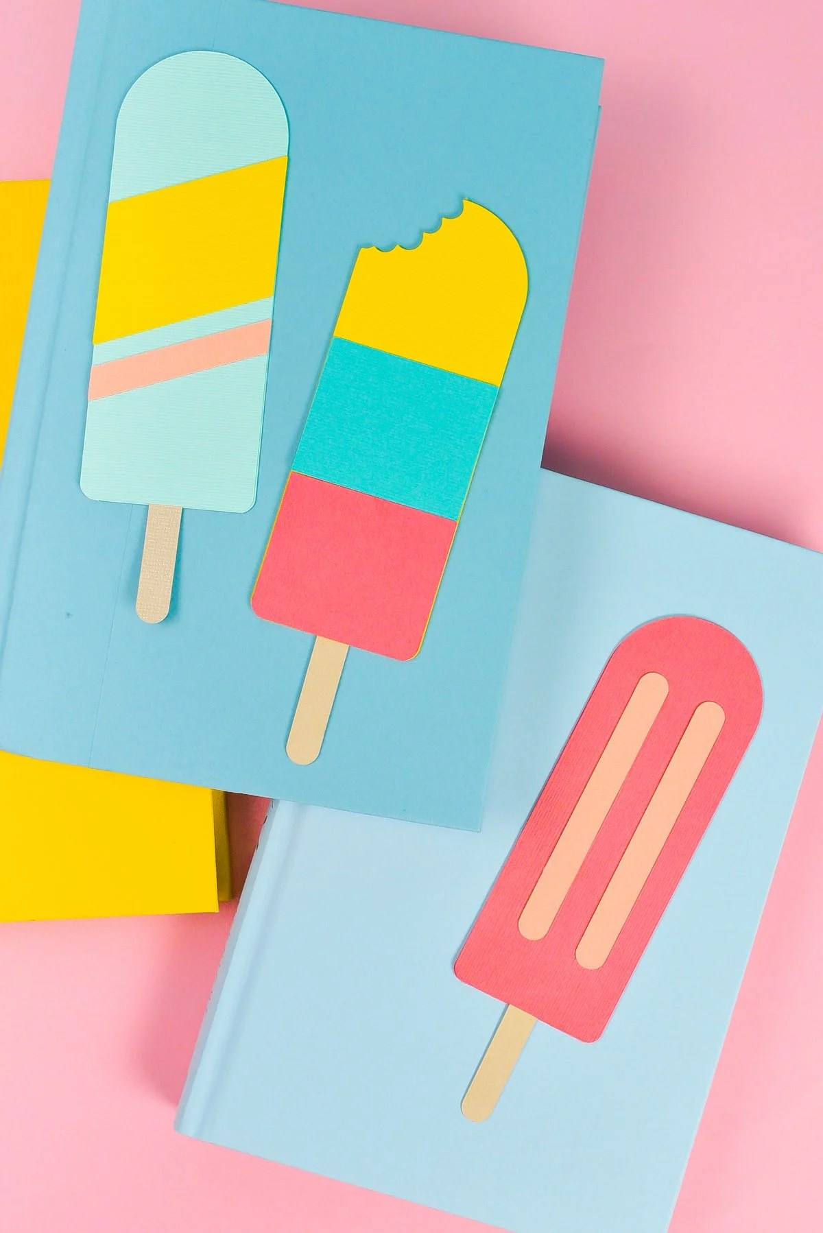 Final popsicle bookmarks styled with bright books on a pink background