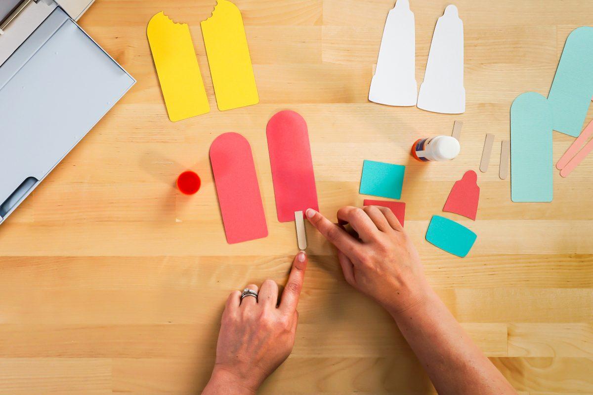 Hands assembling popsicle bookmarks