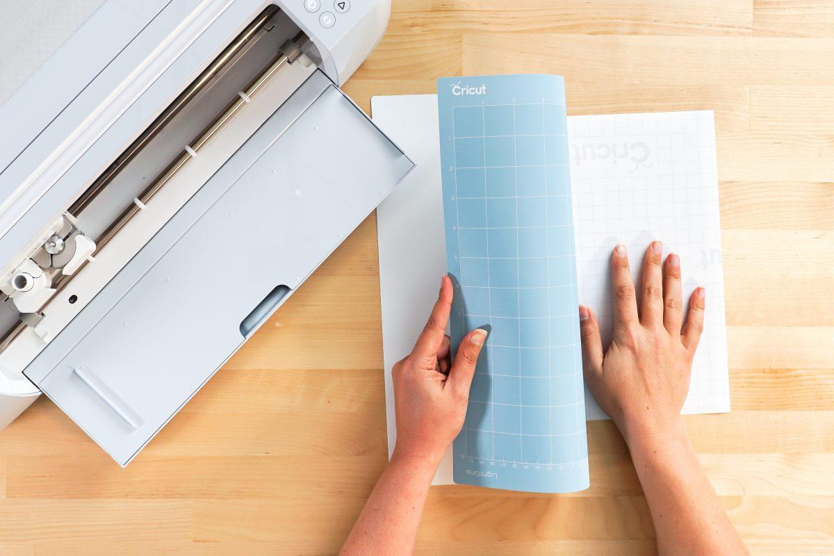 Hands peeling away mat from sticker sheet