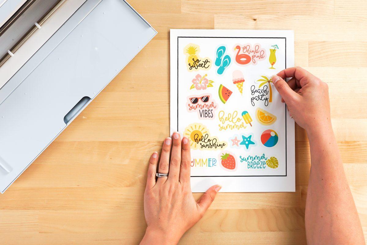 Hands peeling up sticker off sticker sheet