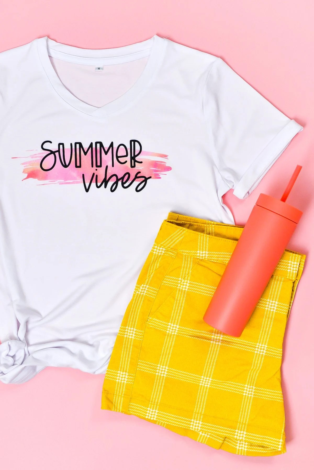 Final Summer Vibes shirt staged with flip flops, water bottle, and shorts on pink background