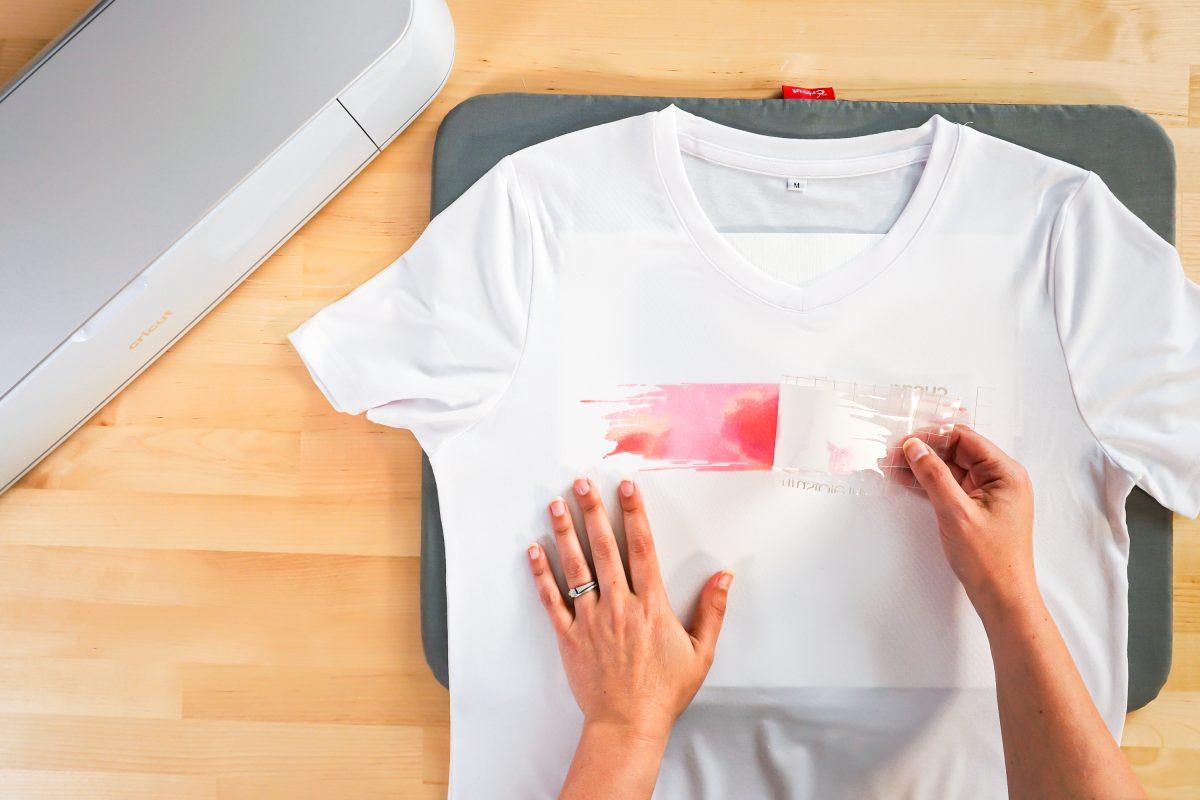 Hands peeling back infusible ink transfer
