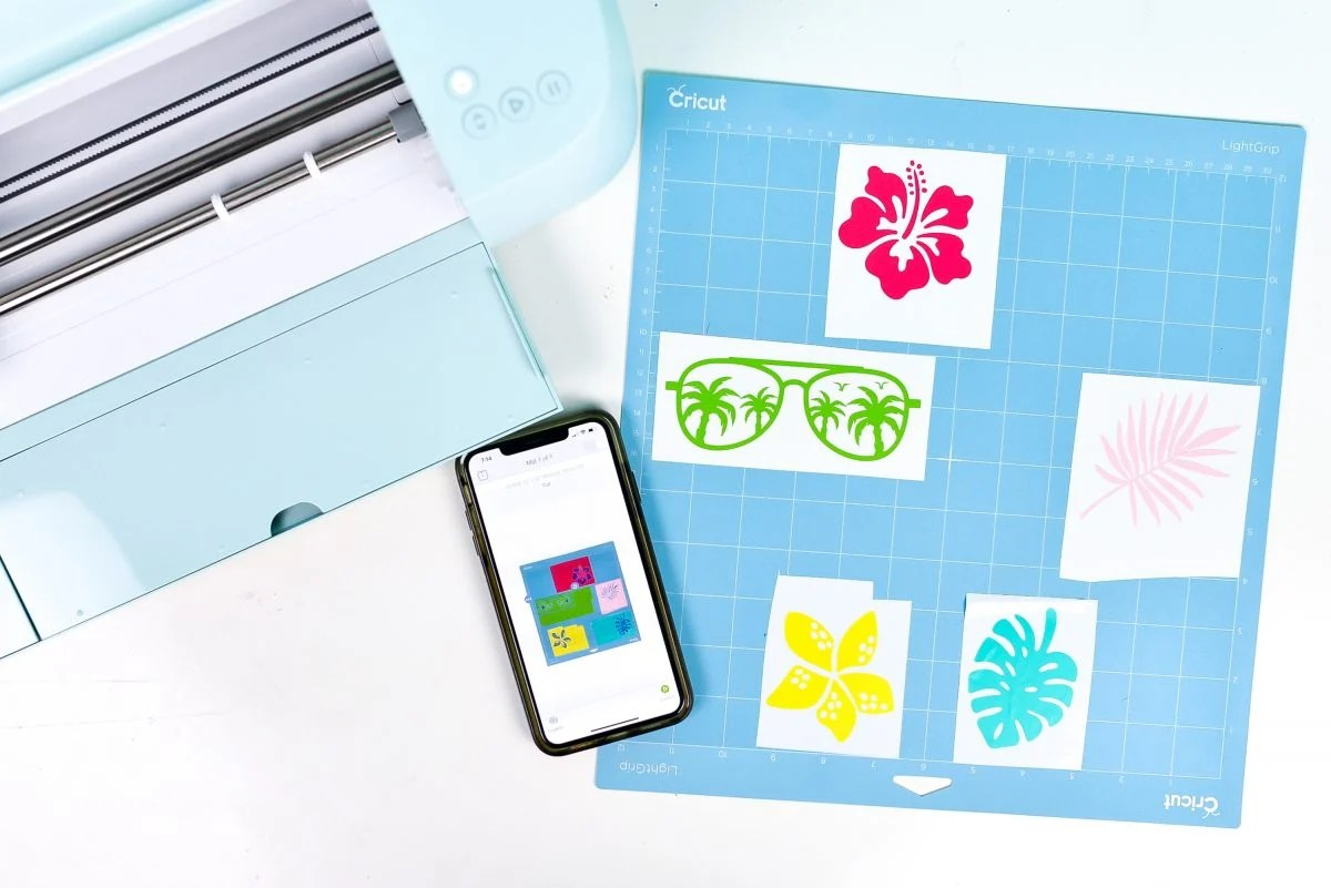 iPhone with Snap Mat screen, plus mat with vinyl scraps and Cricut Explore 3