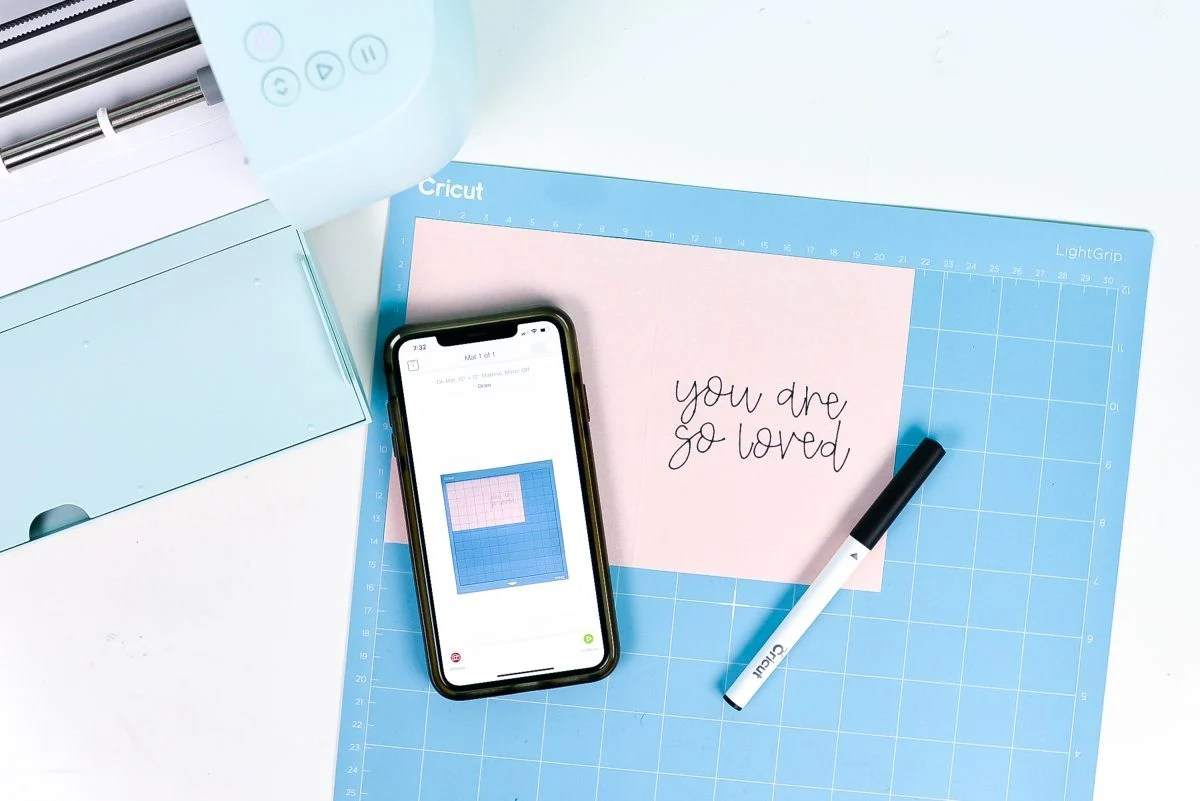 iPhone with Snap Mat screen, plus mat with card and writing and Cricut Explore 3