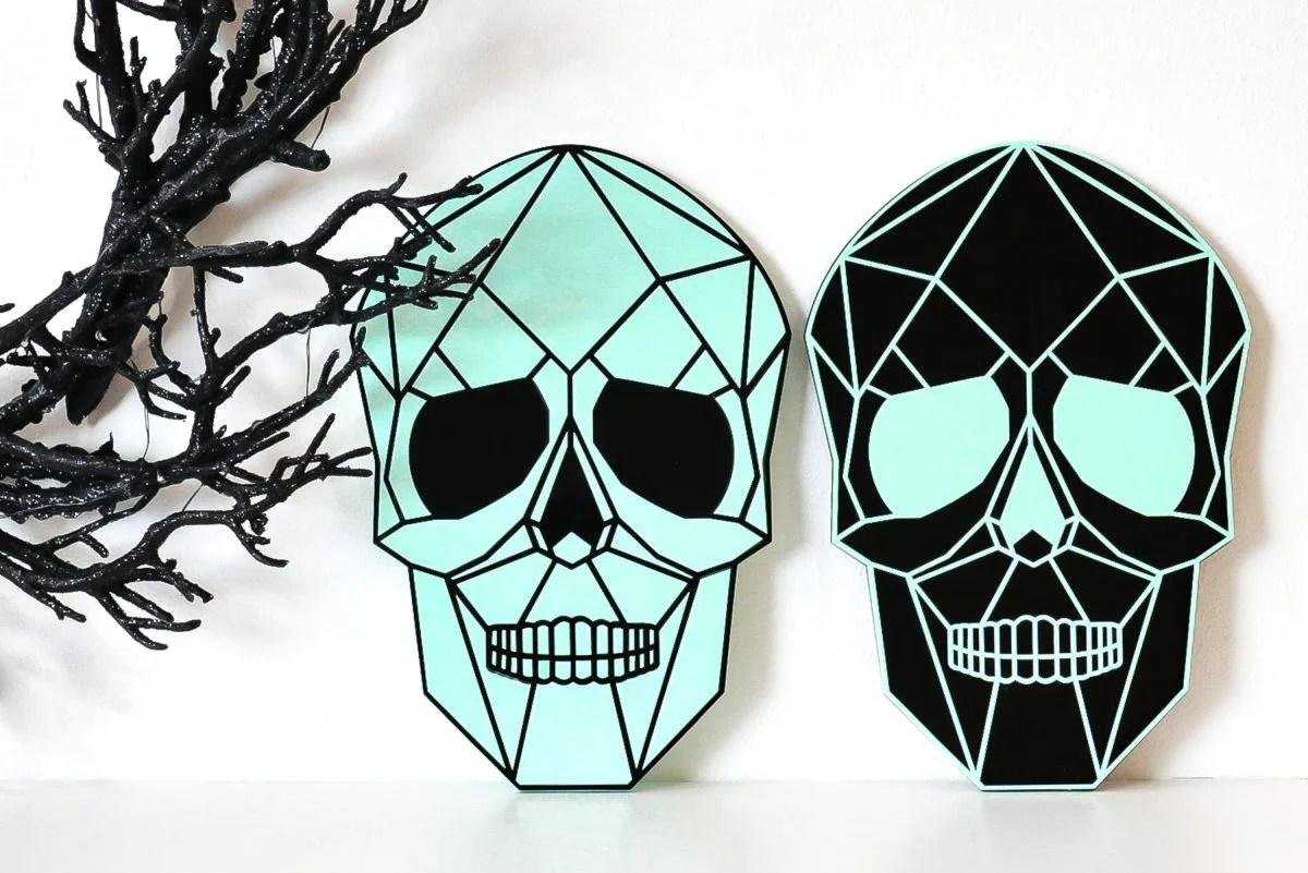 Two skulls on shelf with creepy Halloween wreath.