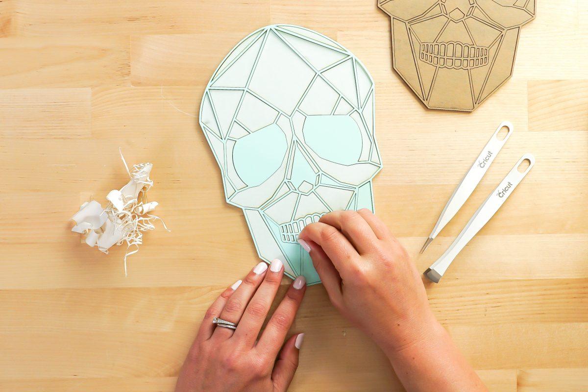 Hands removing the masking from the light blue skull