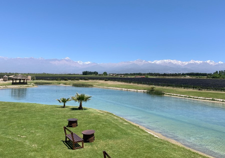 Sunny day with lake, Andes mountains, and a sitting area at Domaine Bousquet in Argentina's Uco Valley.