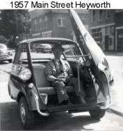 History Mystery Photo #5 The Heyworth Public Library holds in it's archive this picture of a man in a three wheeled vehicle on Main St. in Heyworth, circa 1957 (according to the digital file name. It was submitted as a digital photo with the file marked as Roseman, 1957. If anyone can give us any clues to this mystery picture, we would be very interested in learning more about the person and vehicle, and to know what was going on in the picture in 1957.