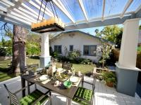 Outdoor Deck and Dining Area Under a Pergola With a