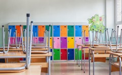 Empty school classroom with chairs on tables and colorful lockers in the background