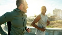Two men running outdoors with city buildings in background