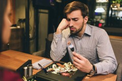 man with inflammatory bowel disease (IBD) looks unhappily at his food