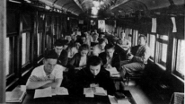 """Students and teacher conducting class in one of the crowded """"School on Wheels"""" railroad car classrooms in 1935."""