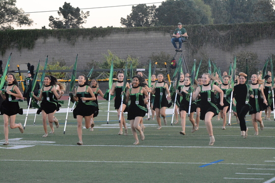 The+color+guard+team+runs+to+the+field+at+the+start+of+the+game.