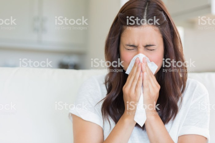 Brunette sneezing in a tissue in the living room