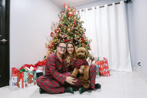 couple by Christmas tree holding goldendoodle